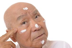 顔にスキンケアをするシニアの写真素材 [FYI03424730]