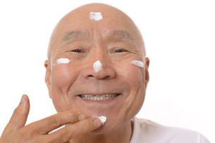 顔にスキンケアをするシニアの写真素材 [FYI03424731]