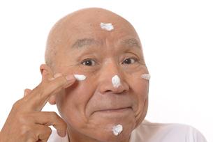 顔にスキンケアをするシニアの写真素材 [FYI03424732]