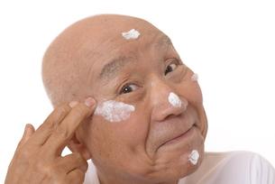 顔にスキンケアをするシニアの写真素材 [FYI03424733]