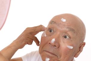 顔にスキンケアをするシニアの写真素材 [FYI03424734]