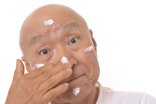 顔にスキンケアをするシニアの写真素材 [FYI03424735]