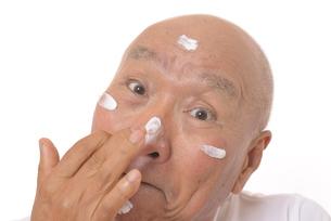 顔にスキンケアをするシニアの写真素材 [FYI03424736]