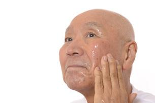 顔にスキンケアをするシニアの写真素材 [FYI03424737]