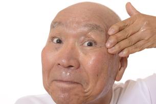 顔にスキンケアをするシニアの写真素材 [FYI03424738]