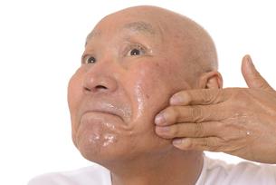 顔にスキンケアをするシニアの写真素材 [FYI03424739]