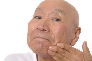 顔にスキンケアをするシニアの写真素材 [FYI03424740]