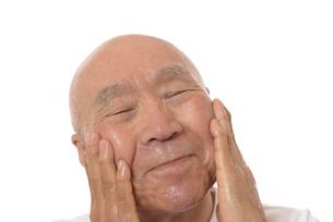 顔にスキンケアをするシニアの写真素材 [FYI03424741]