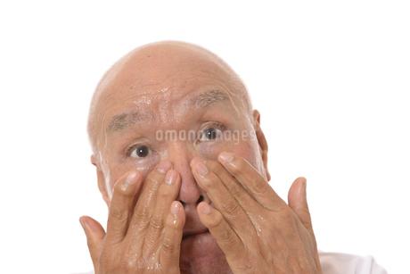 顔にスキンケアをするシニアの写真素材 [FYI03424742]