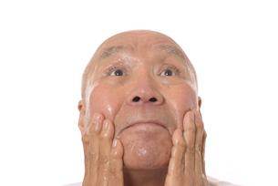 顔にスキンケアをするシニアの写真素材 [FYI03424743]