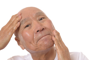 顔にスキンケアをするシニアの写真素材 [FYI03424744]