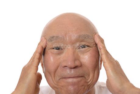 顔にスキンケアをするシニアの写真素材 [FYI03424746]