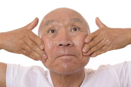 顔にスキンケアをするシニアの写真素材 [FYI03424747]