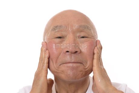 顔にスキンケアをするシニアの写真素材 [FYI03424749]