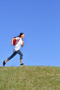 青空で走る小学生の女の子(ランドセル)の写真素材 [FYI03425343]