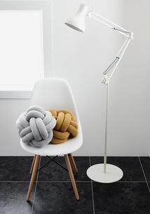 白いフロアライトとクッションが置かれた白い椅子の写真素材 [FYI03428073]