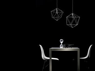黒い壁前にある白いダイニングセットとペンダントライトの写真素材 [FYI03428075]