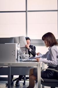 新聞紙に隠れながらいやらしい目で女性社員を見る上司の写真素材 [FYI03428078]