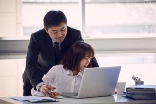 パソコンを操作する手を触ろうとする上司と嫌がる女性社員の写真素材 [FYI03428082]