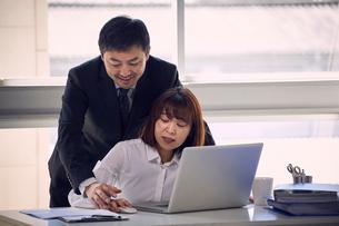 パソコンを操作する手を触ろうとする上司と嫌がる女性社員の写真素材 [FYI03428083]