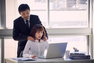 肩もみをして体に触れる上司と嫌がる女性社員の写真素材 [FYI03428084]