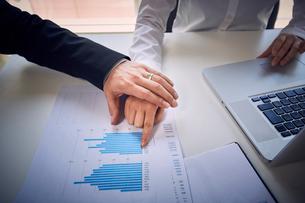 女性社員の資料を指す手を握りに行く上司の写真素材 [FYI03428085]