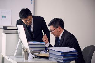 大量の仕事を押し付ける上司と苦い顔をする部下の写真素材 [FYI03428089]