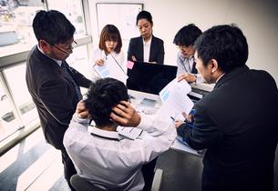 5人の上司から仕事の指摘を受け頭を抱える若手社員の写真素材 [FYI03428093]