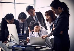 5人の上司から仕事の指摘を受け頭を抱える若手社員の写真素材 [FYI03428094]