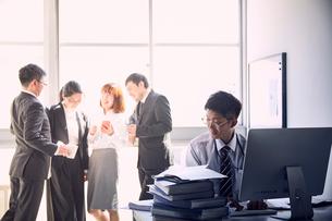 一人で大量の仕事をする若手社員と仕事をせず盛り上がる上司達の写真素材 [FYI03428095]