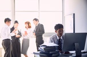 一人で大量の仕事をする若手社員と仕事をせず盛り上がる上司達の写真素材 [FYI03428096]