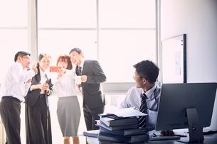 一人で大量の仕事をする若手社員と仕事をせず盛り上がる上司達の写真素材 [FYI03428097]