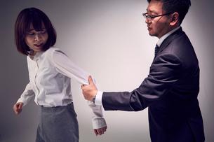 無理に連れて行こうと腕を掴む上司と嫌がる女性社員の写真素材 [FYI03428101]