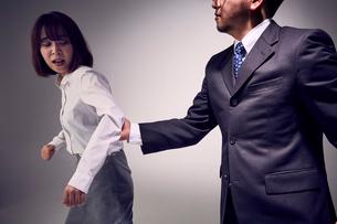 無理に連れて行こうと腕を掴む上司と嫌がる女性社員の写真素材 [FYI03428102]
