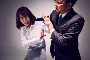 無理に連れて行こうする上司と激しく抵抗する女性社員の写真素材 [FYI03428103]
