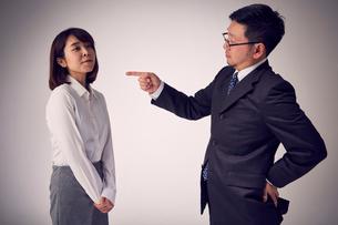 上司から説教を受けているのに反省が見えない女性社員の写真素材 [FYI03428104]