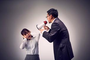 メガホンで説教する上司と耳をふさぐ女性社員の写真素材 [FYI03428106]