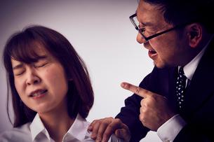 耳元で大声で説教する上司と辛そうな女性社員の写真素材 [FYI03428107]