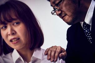 体に触れてくる上司と嫌がる女性社員の写真素材 [FYI03428109]