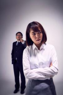 上司の指摘に嫌気がさし無視する女性社員の写真素材 [FYI03428111]