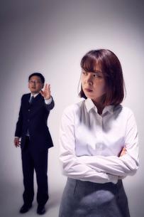 上司の指摘に嫌気がさし無視する女性社員の写真素材 [FYI03428113]