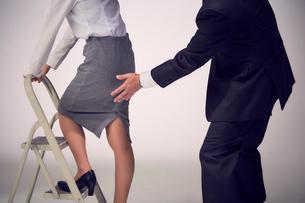 脚立に登る女性社員のお尻を触る上司の写真素材 [FYI03428114]