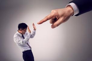 大きな手に指を指され圧倒される男性社員の写真素材 [FYI03428116]