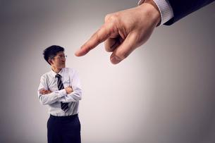 大きな手に指を指されるも対抗する男性社員の写真素材 [FYI03428117]