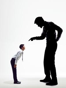 大きな上司の影に説教され謝罪する男性社員の写真素材 [FYI03428118]