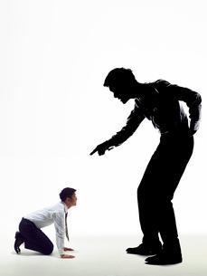 大きな上司の影に説教され土下座して謝罪する男性社員の写真素材 [FYI03428119]
