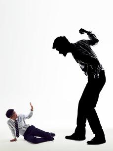 大きな上司の影に暴力を受け服従する男性社員の写真素材 [FYI03428120]