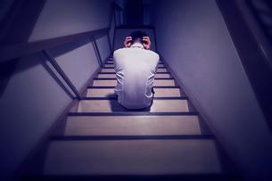 終業時刻を超えて一人で階段で頭を抱える男性社員の写真素材 [FYI03428129]