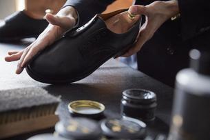 指で靴にクリームを塗る靴磨き職人の写真素材 [FYI03428136]