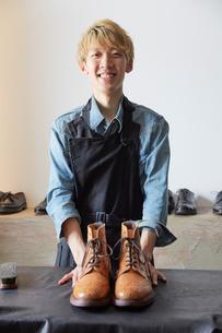 靴の修理を終えた職人の写真素材 [FYI03428140]
